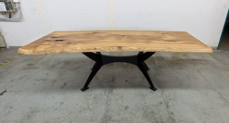 Wir sehen eine Baumscheiben-Tischplatte mit Gestell